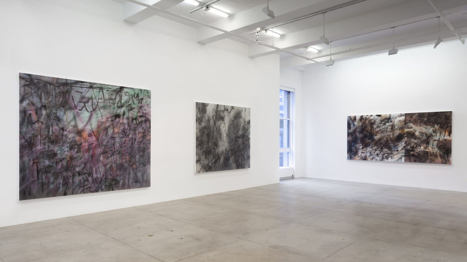 3 abstract paintings hang in a white gallery space with a window.