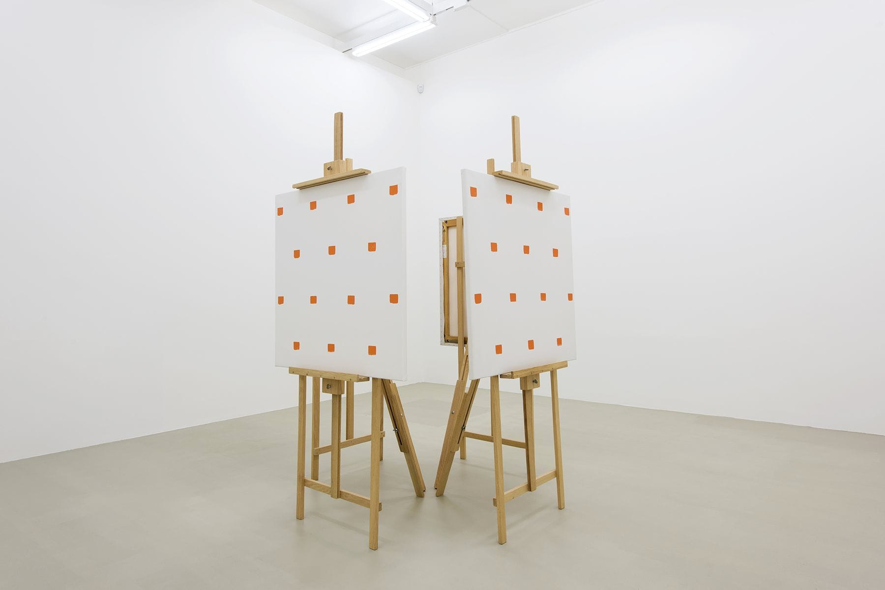 Gallery view of hour outwardly facing wooden easels displaying four canvases, with rows of equidistant square red brush strokes.