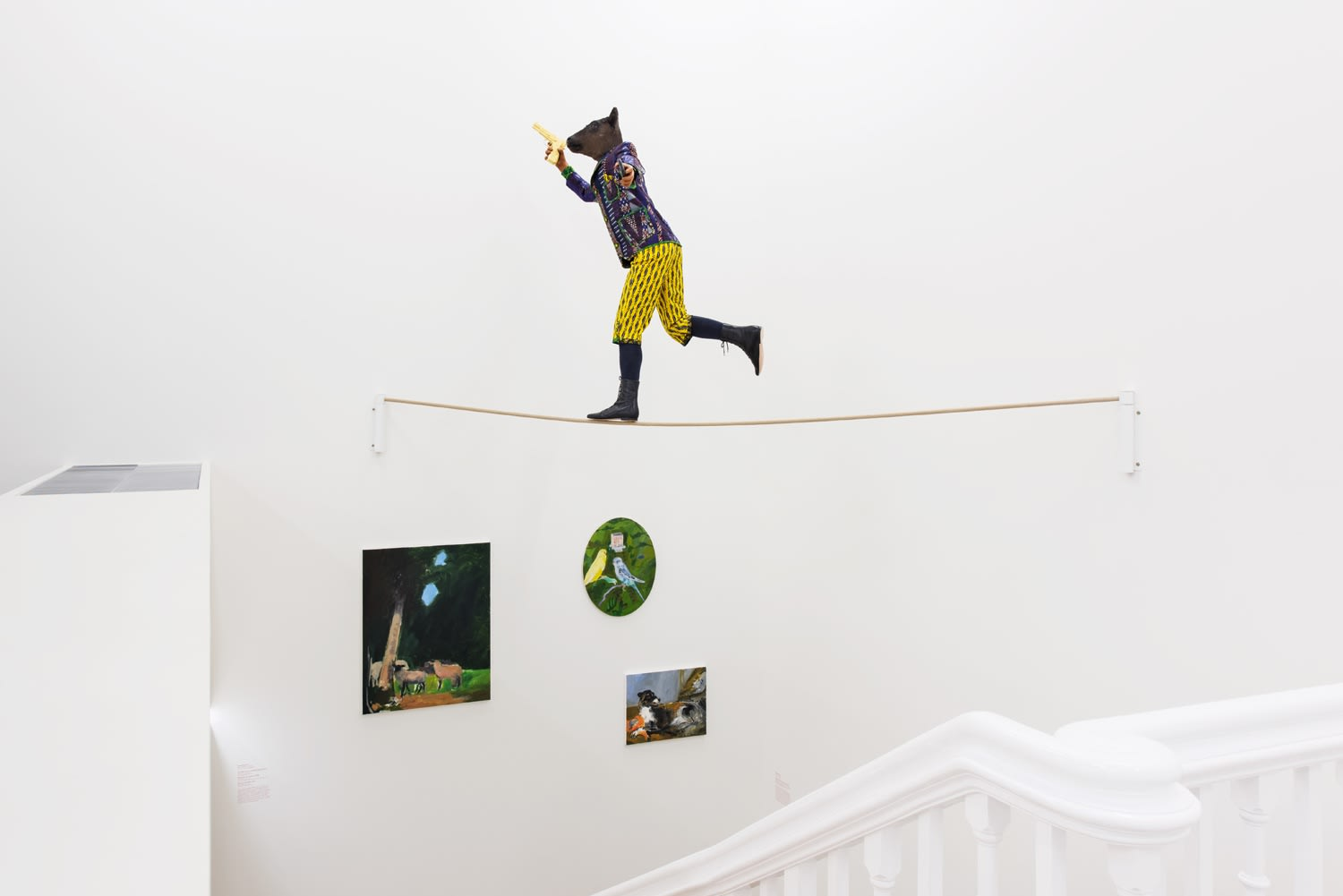 Installation view of miniature figure with a cow head and human body in wildly colored garments on a tightrope clutching a gun.