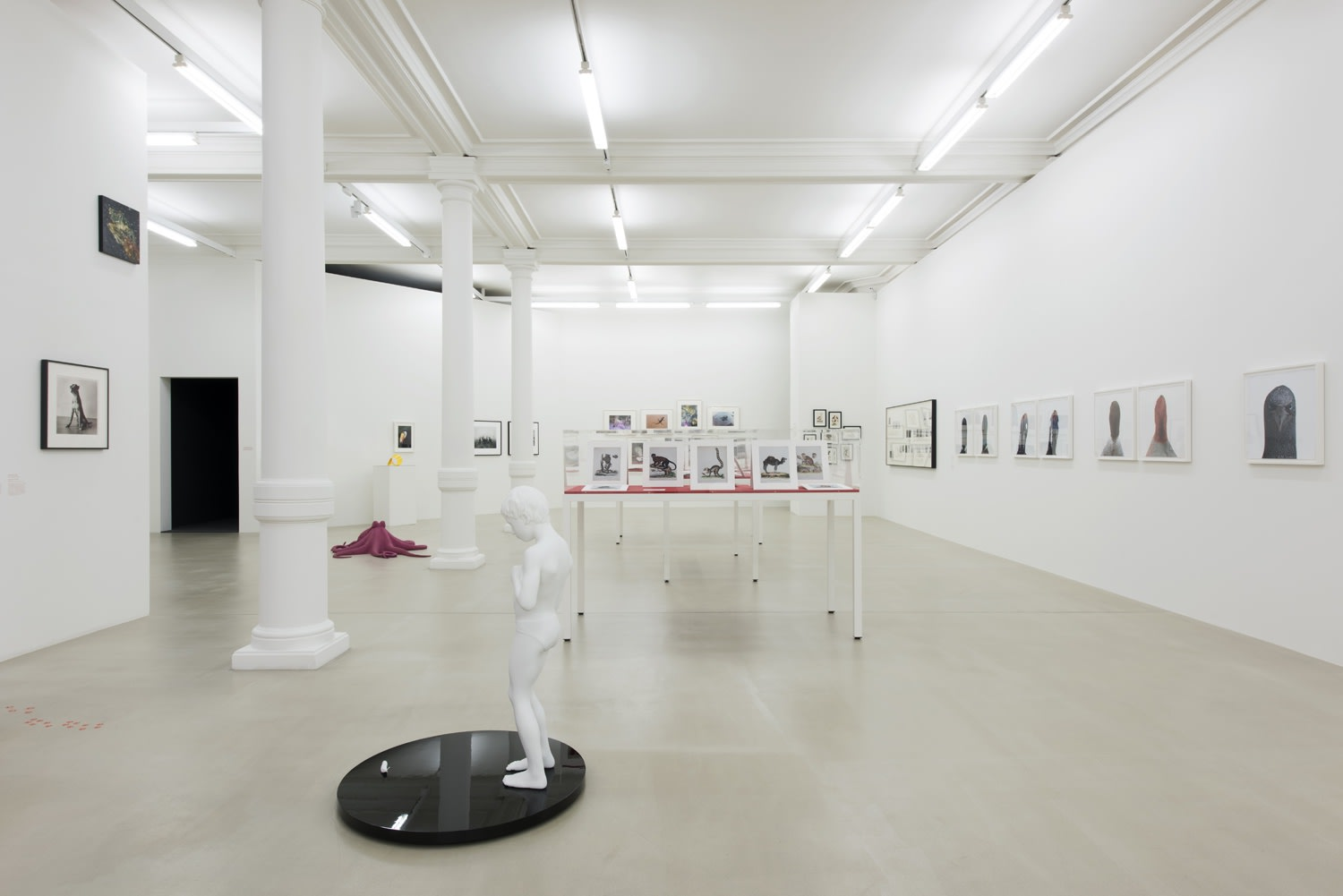 Gallery installation view of gallery as whole including a sculpture of a child on a black circular platform.