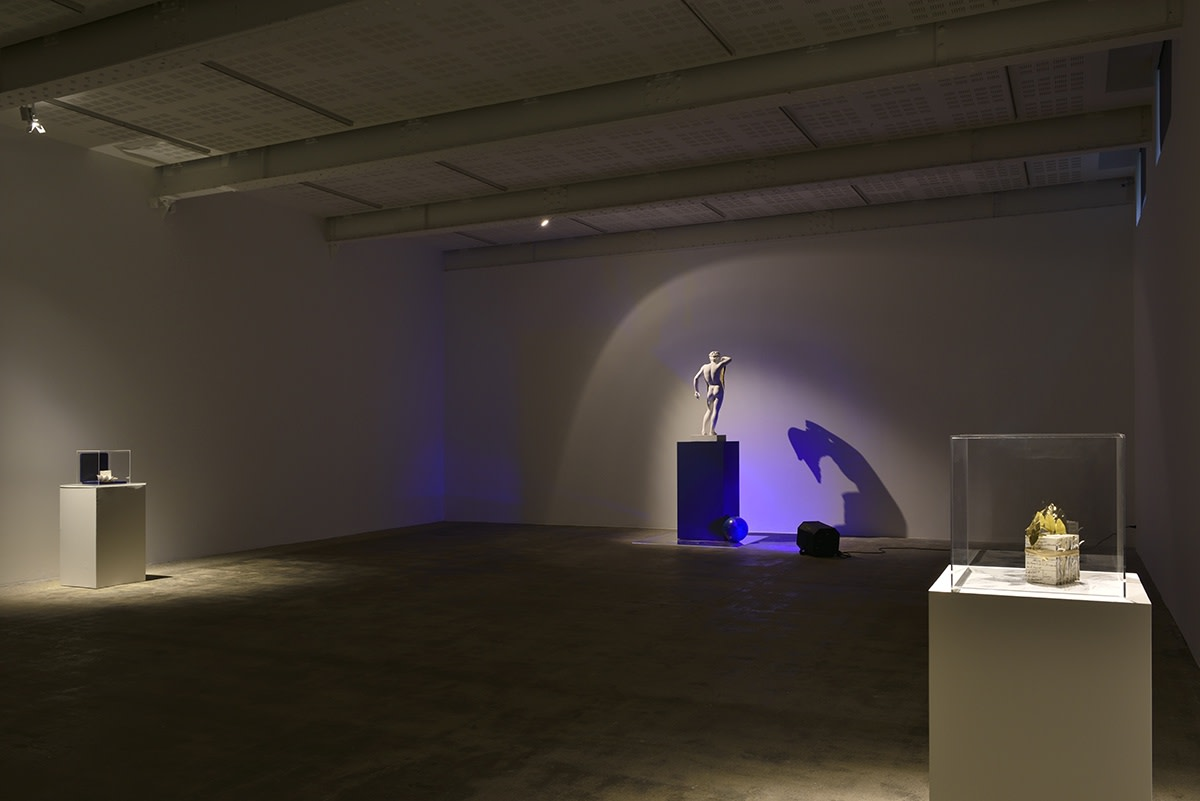 Gallery installation, blue light hits a small Greek statue creating a a hunched shadow against the wall.