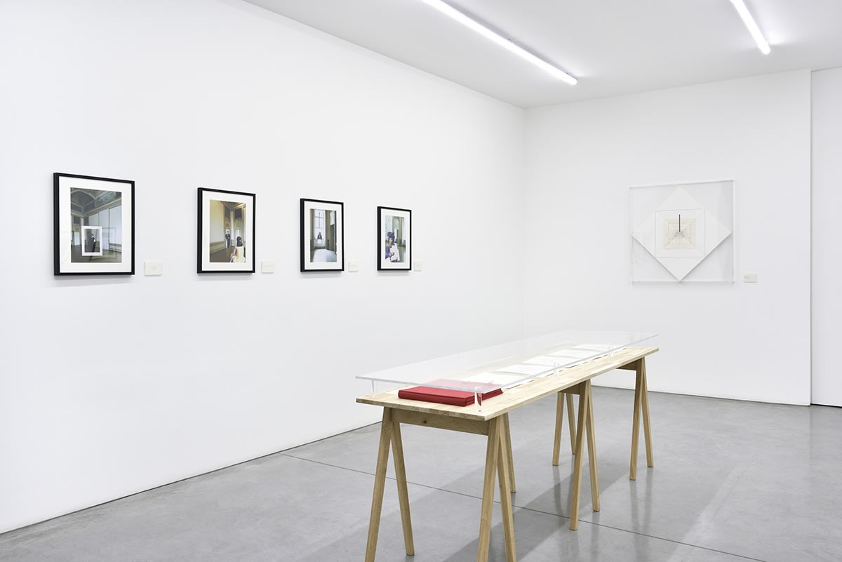 A well lit gallery displays framed works on the wall and a display table in the center of the room.