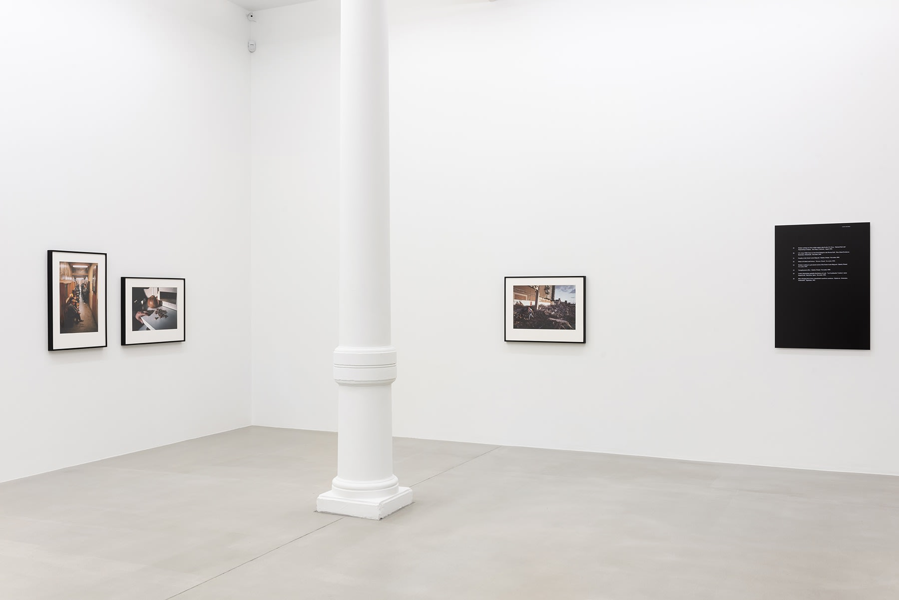 Four small photographs on gallery wall with a pillar between them.