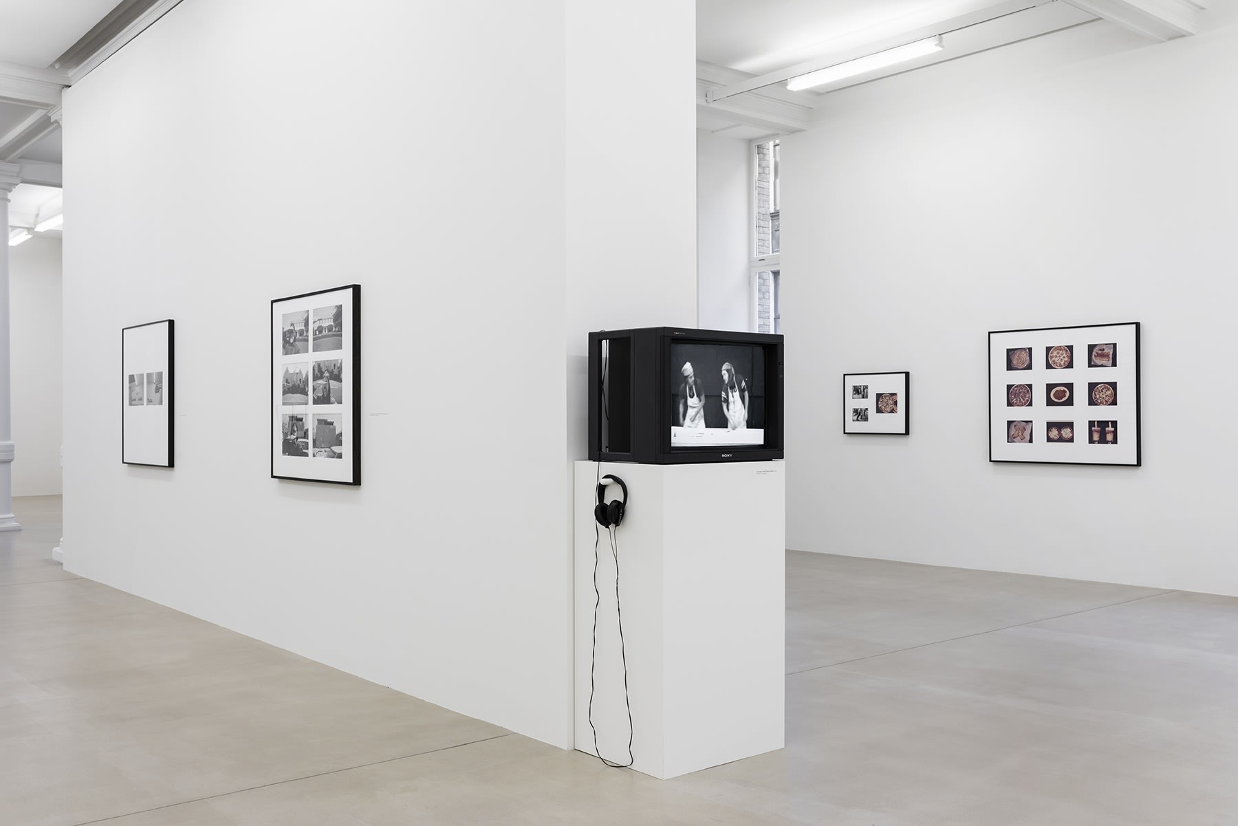 A cathode-ray tube tv displaying content stands on a pedestal, surrounded by several black and white photographs on walls.