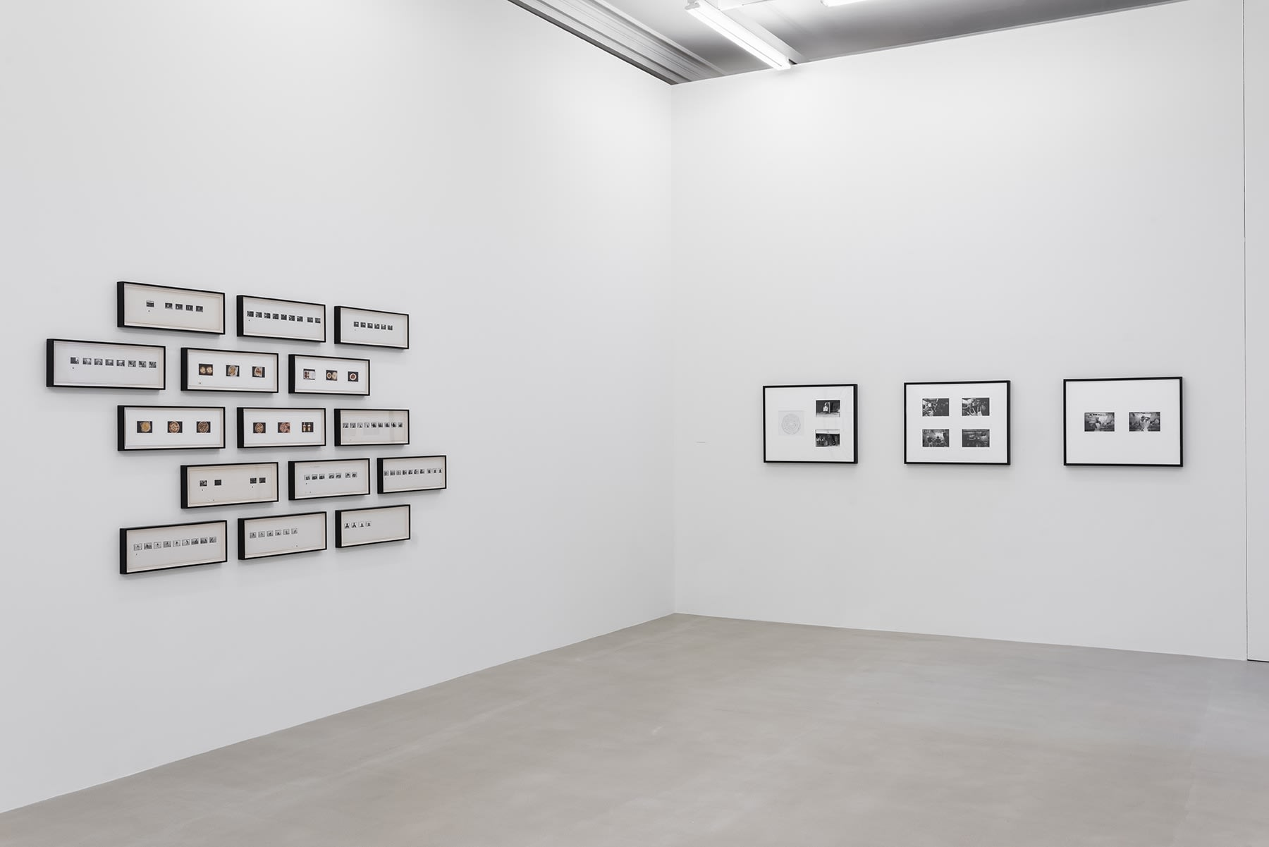 15 narrow frames holding small photographs hang three-by-three on one wall, beside one wall of large rectangular framed black and white photographs.
