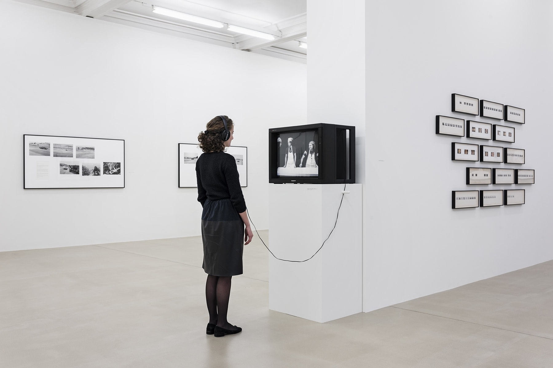 A person with headphones watches content on a cathode-ray tube tv displayed on a pedestal, surrounded by several black and white photographs on walls.