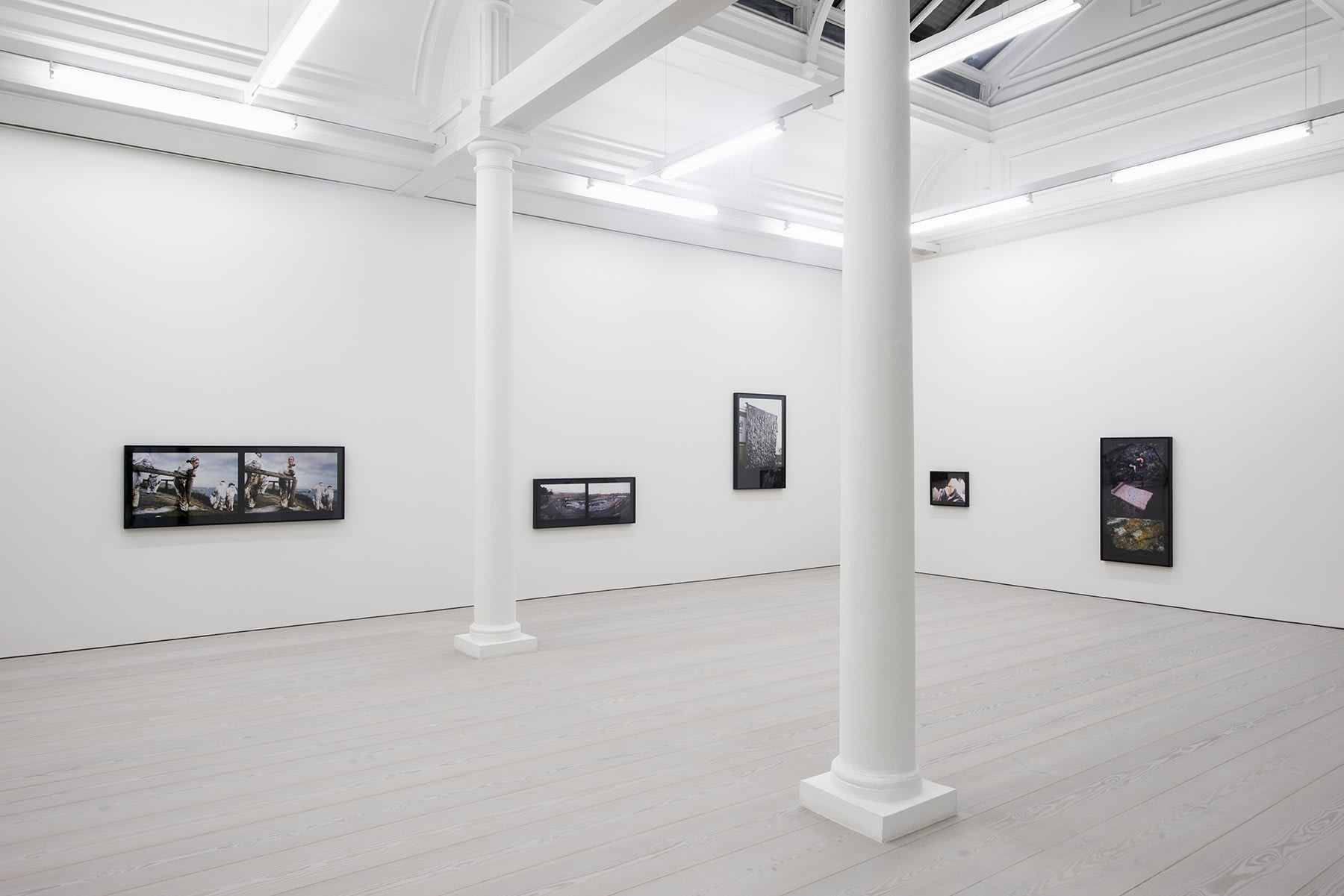 A set of color photographs hang on three white walls. One on the far left is a photograph of men at work outside; the rest are images of industrial by-products.