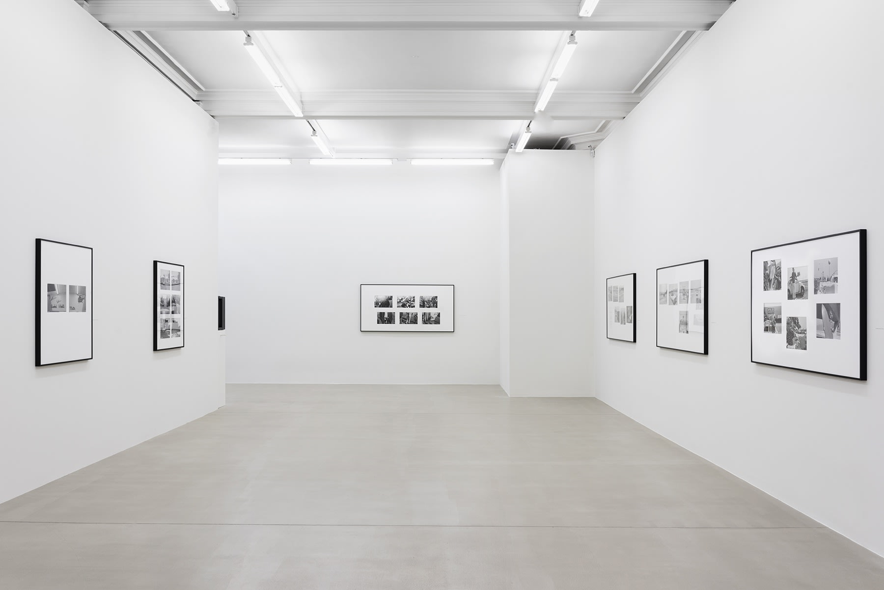 A set of black and white photographs hang on three white walls.