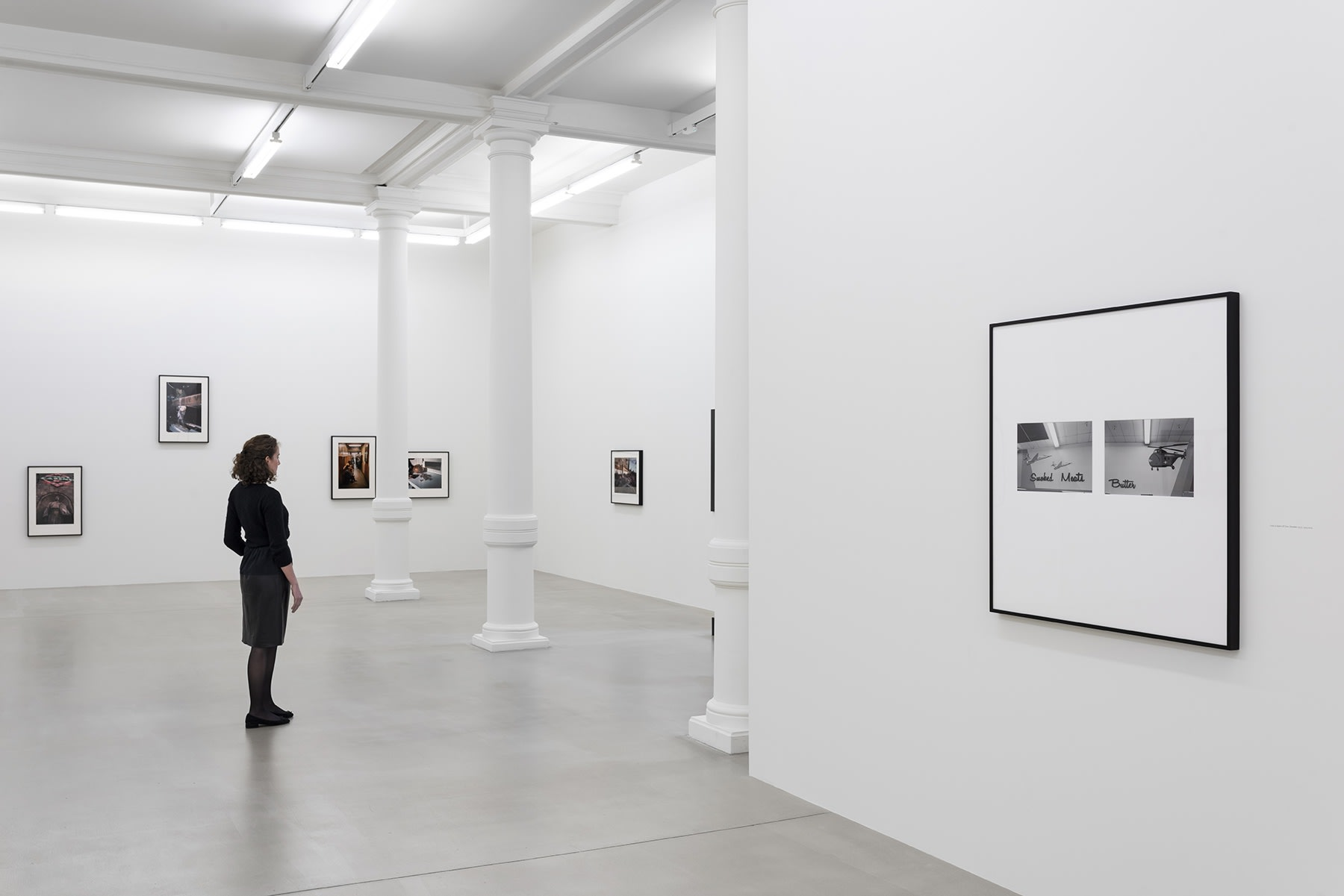 A person stands in front of a display of photographs on 2 walls.
