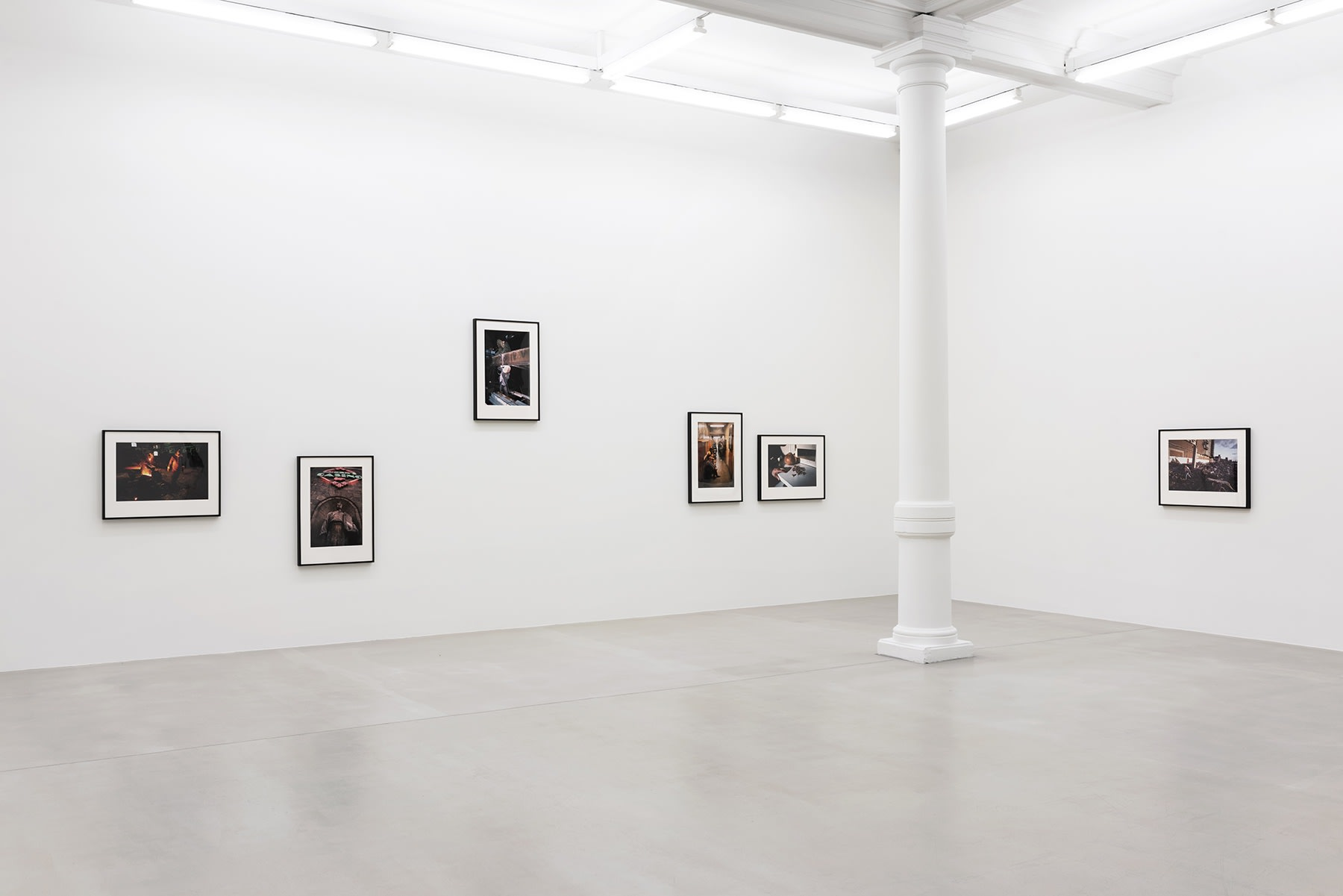 Five color photographs hang on a wall opposite another wall, where one photograph hangs close to a white column.