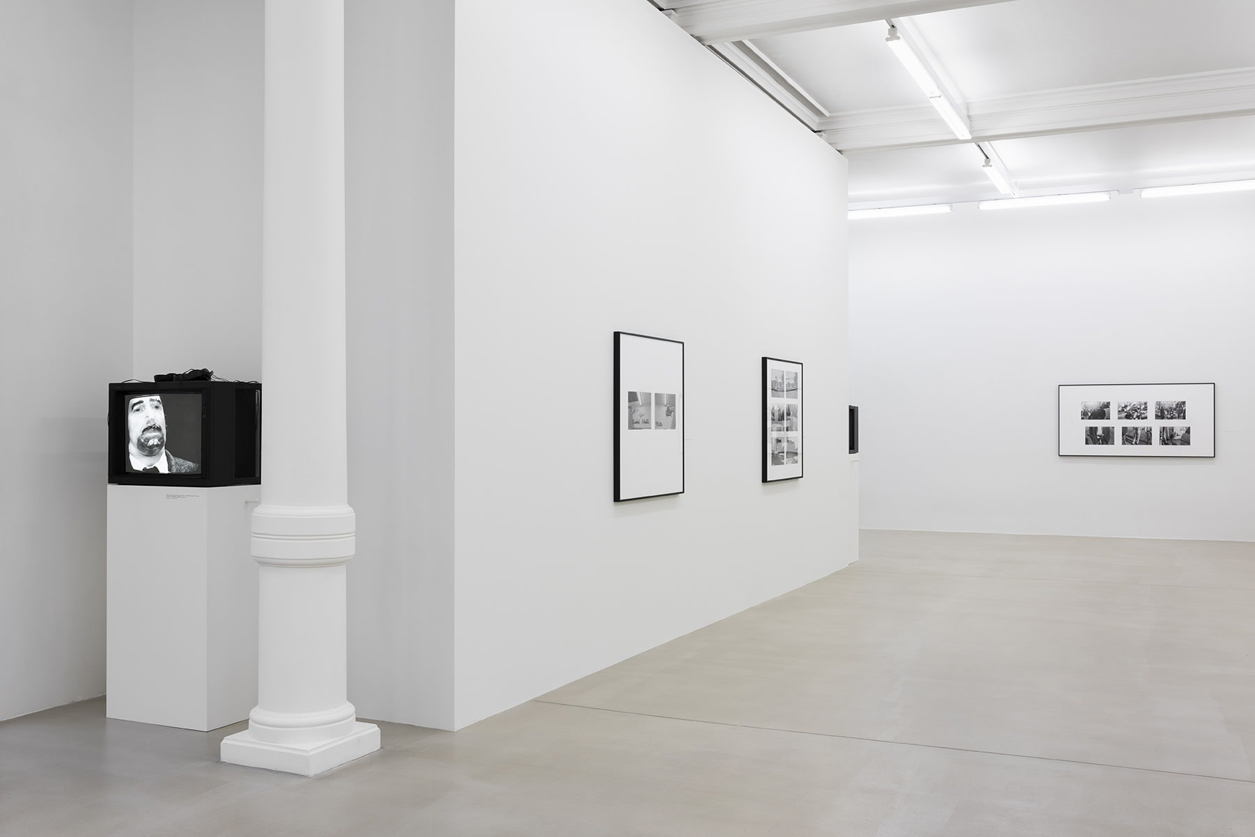 A cathode-ray television displays a man in black and white on a pedestal behind a wall on which 2 frames of black and white photos are hung. This wall is perpendicular to another wall with black and white photos on it.