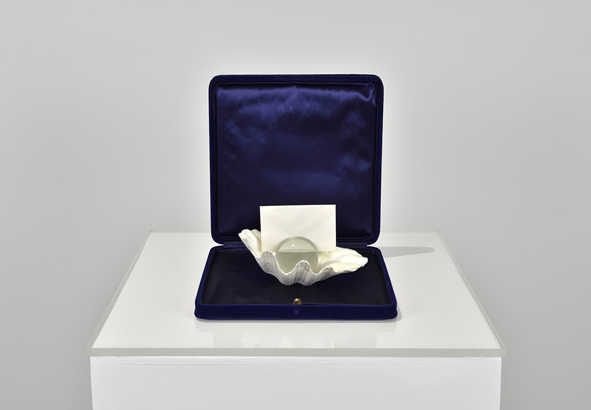 a glass ball and an envelope inside a sea shell all enclosed in a jewel case; work by Giulio Paolini