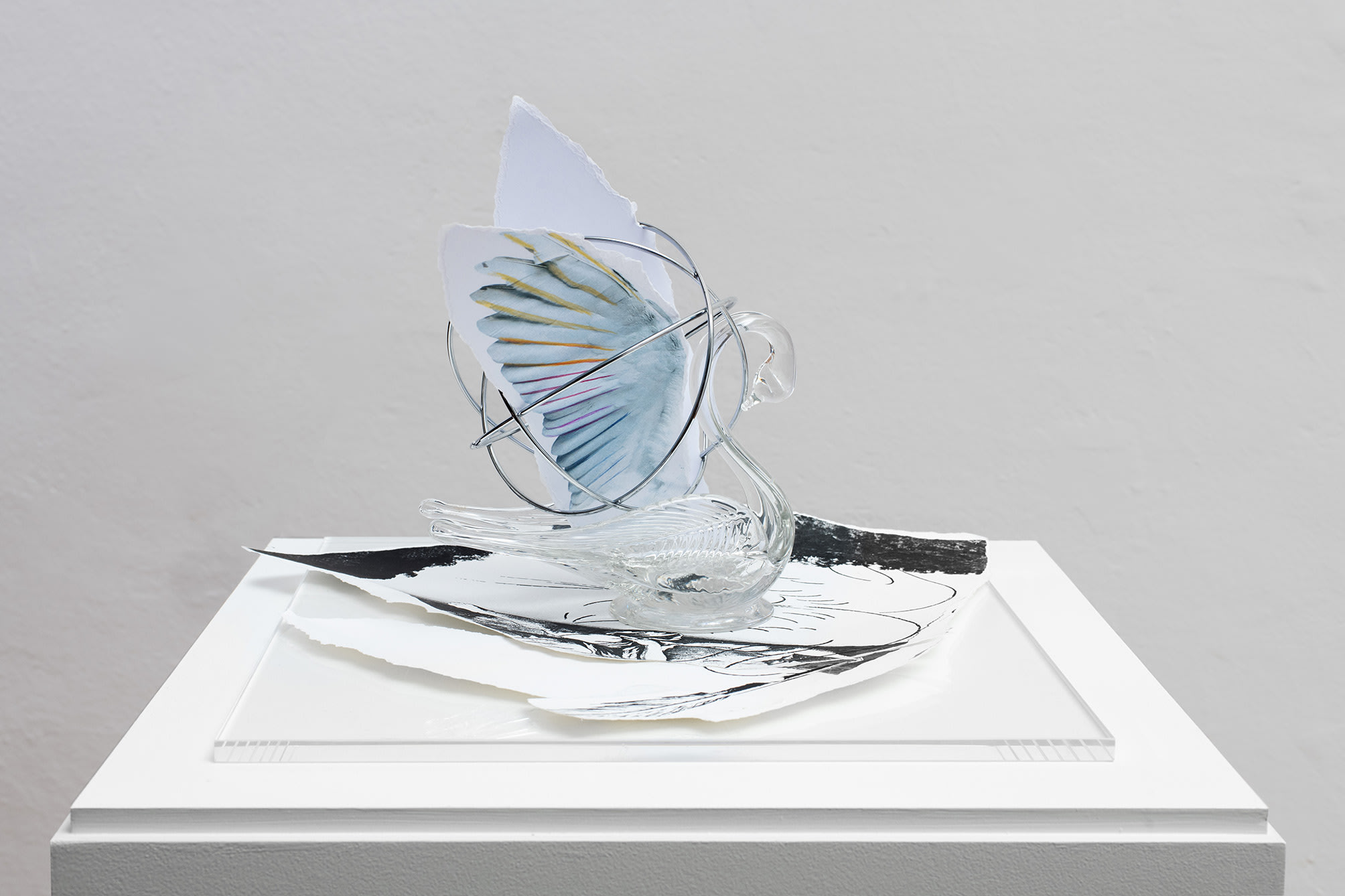 a glass swan with paper wings sits on a drawing; work by Giulio Paolini
