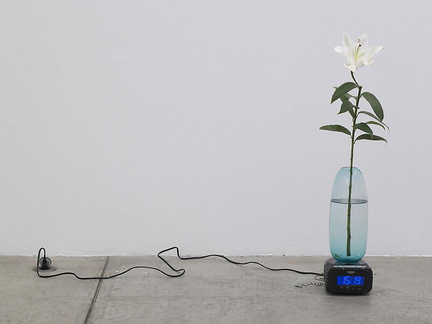 A lily in a vase sits on a clock plugged into the floor.