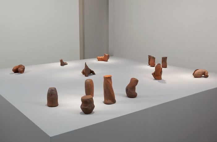 Small amorphous wooden sculptures on large pedestal.