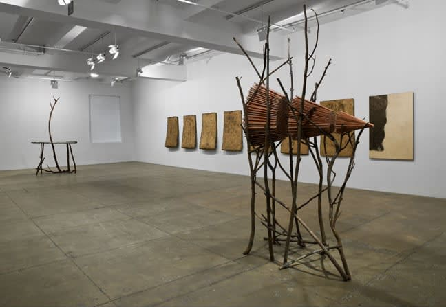 Gallery view of sculpture made of sticks cradling a a pyramid of wood.