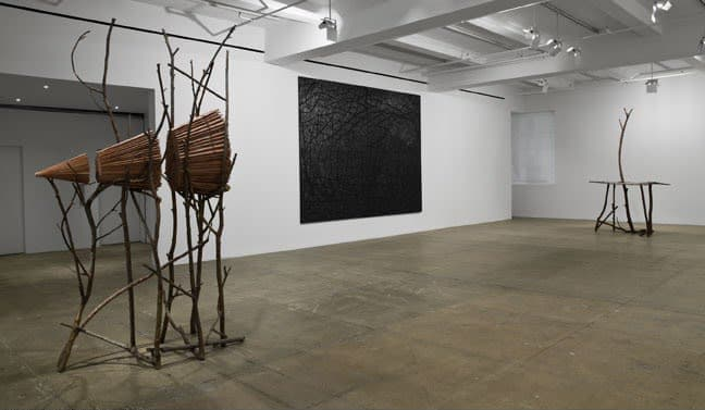 View of gallery. On the far right is a sculpture made of tree branches holding a cone built from wood. On the wall is a textured black painting. On the left is another sculpture made of twigs resembling a table with one branch sticking up through the midd