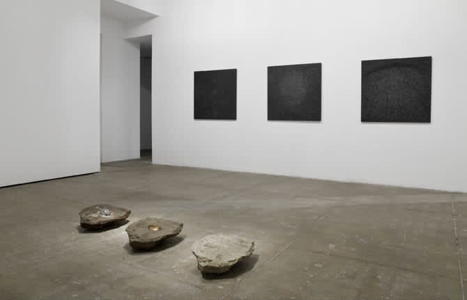 Gallery view. Three flat-topped rocks are parallel to three textured black paintings mounted on the wall.