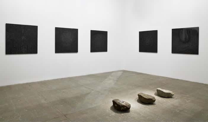 multiple black textured paintings mounted in gallery. Three oval shaped rocks sit facing the far wall in the middle of the floor.