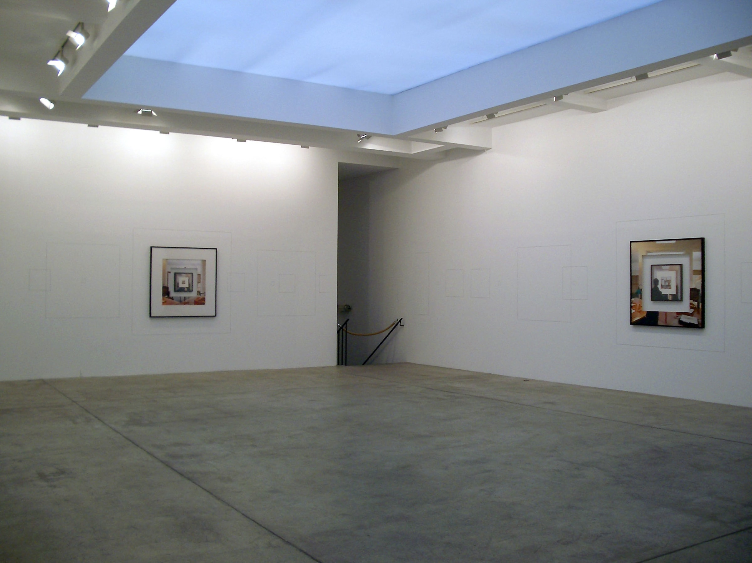 Two framed photographs on two separate walls of a gallery.