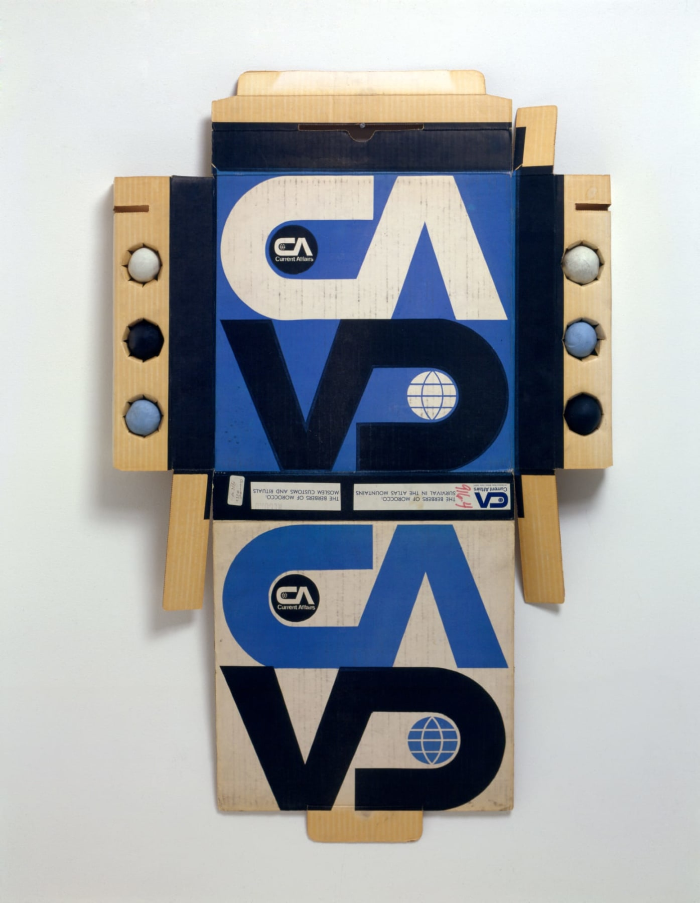 Cardboard packaging with a repeated logo printed in white, black and blue with the letters C A V D.