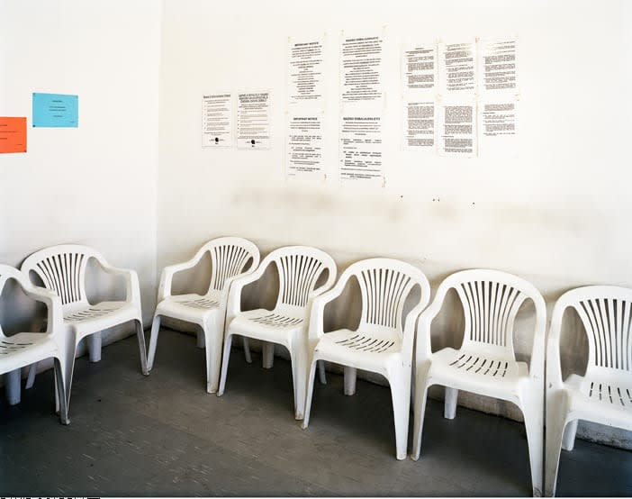 A series of plastic park chairs lined against two walls; the walls have posters of text on them.