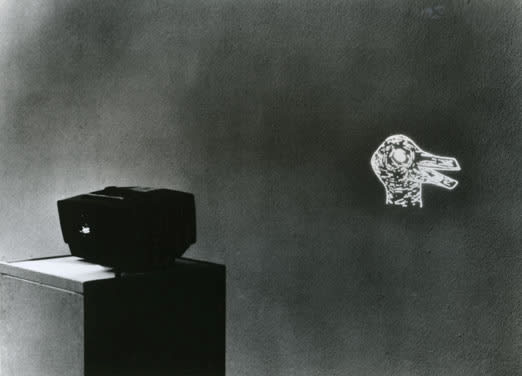Grainy black and white image of a slide projector on a pedestal casting the image of an illustrated duck head.