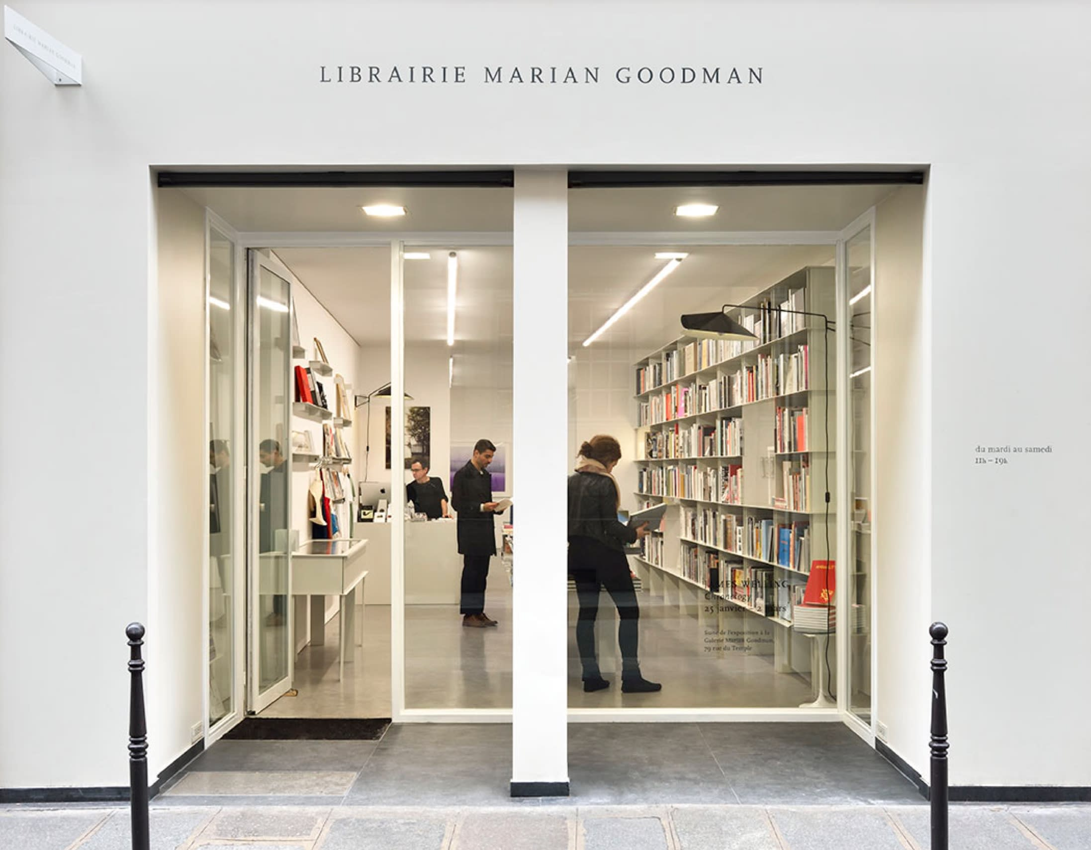 Glass doors that look into a bookstore, with the words Librairie Marian Goodman stenciled in black above the white-walled storefront.