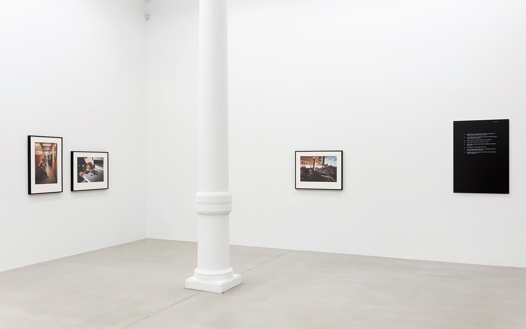 Gallery view of four photographs mounted on wall, pillar in the middle.