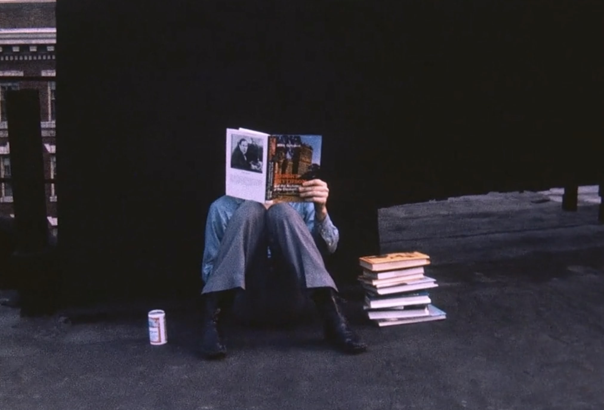 """A still from the film """"Bob with Books"""" of Robert Smithson reading books"""