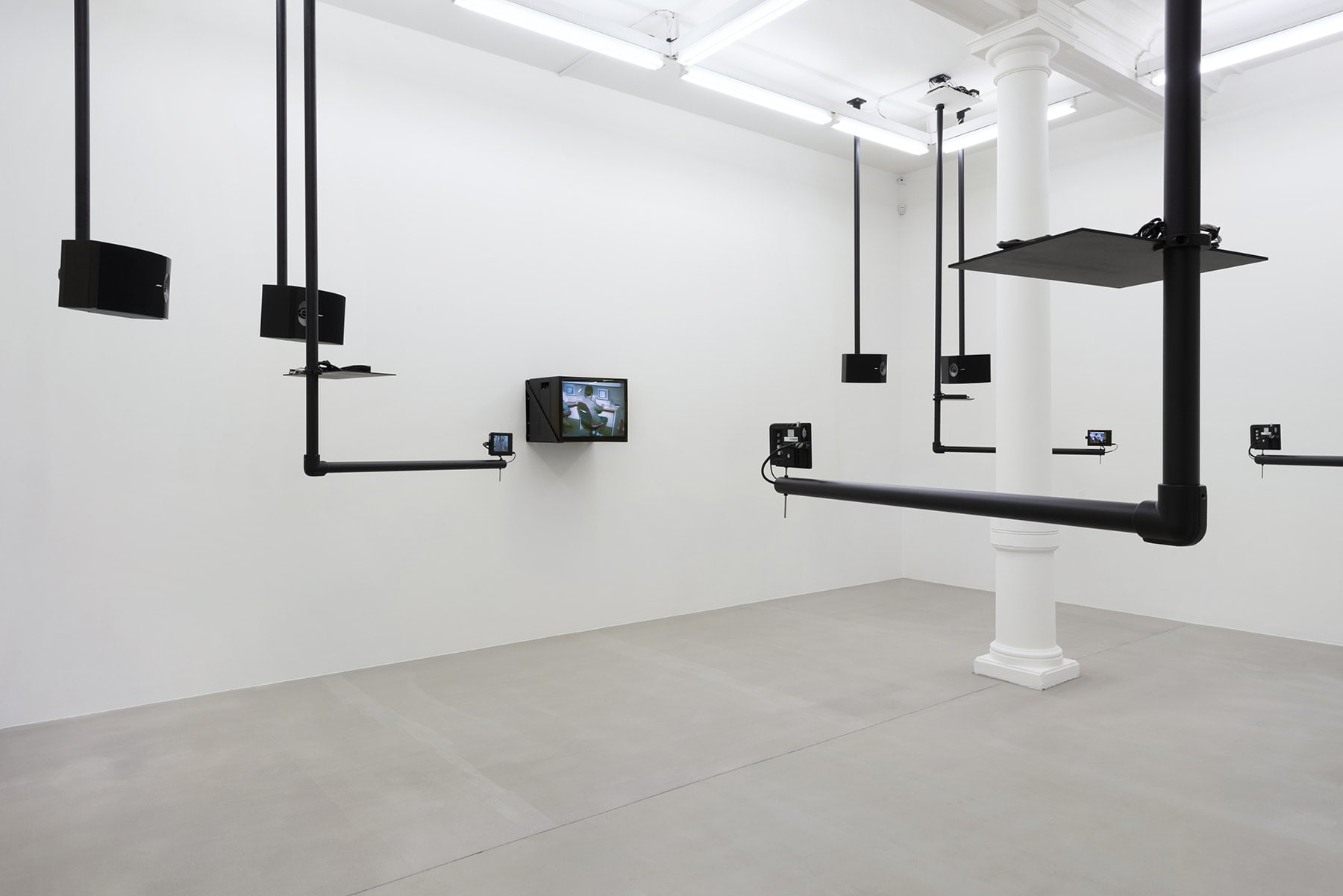 Installation: screens and speakers rest on suspended black platforms.