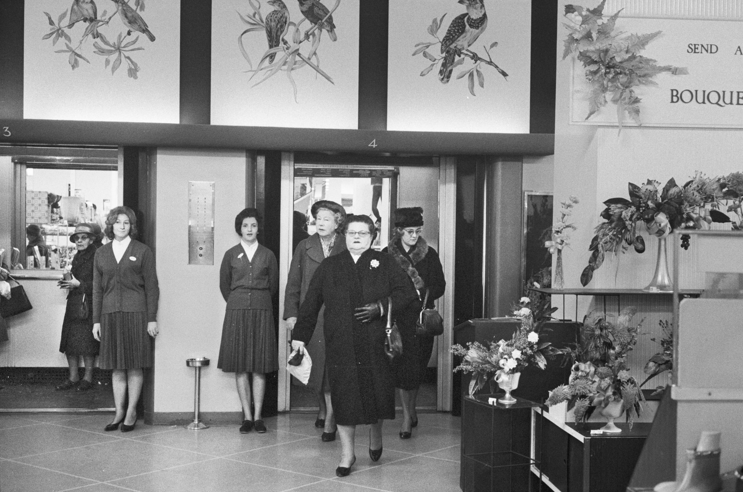 Black and white image of people in full coats and matching pocketbooks and shoes entering a high-end flower store. Store clerks wait by the door.
