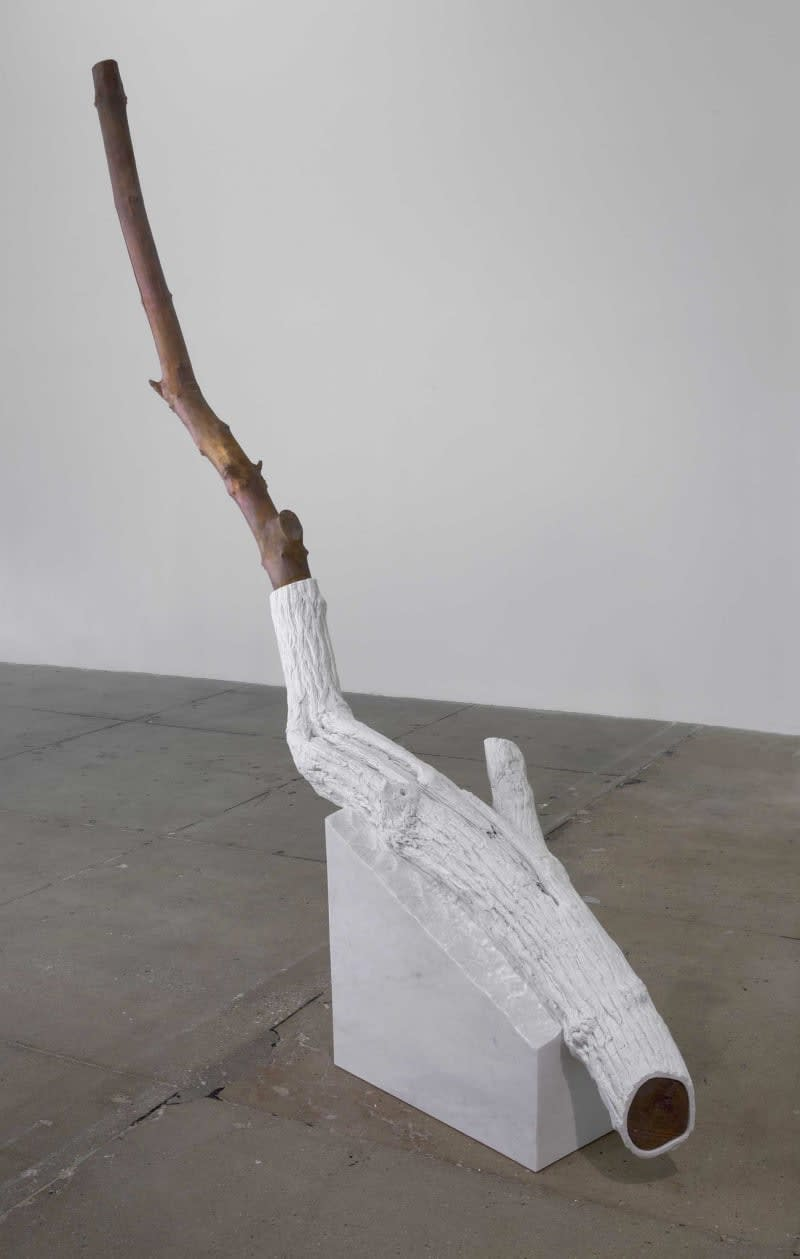 Gallery view of a tree branch, half of which is natural wood, the other half painted white. The object is set on a marble triangle.