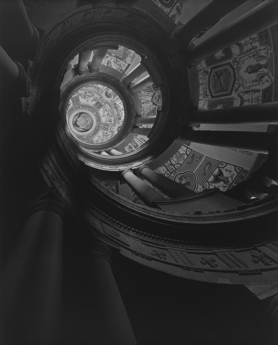 Black and white photograph of an upward view of a circular architectural spire with columns and fresco paintings in the grotesque style.