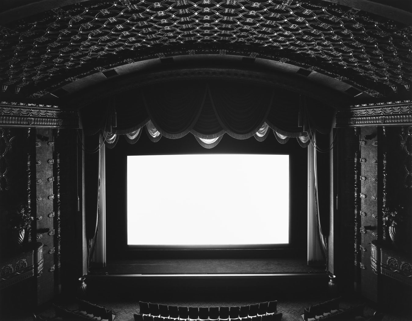 Black and white photograph of a balcony view of a darkened theater stage with a large white screen.