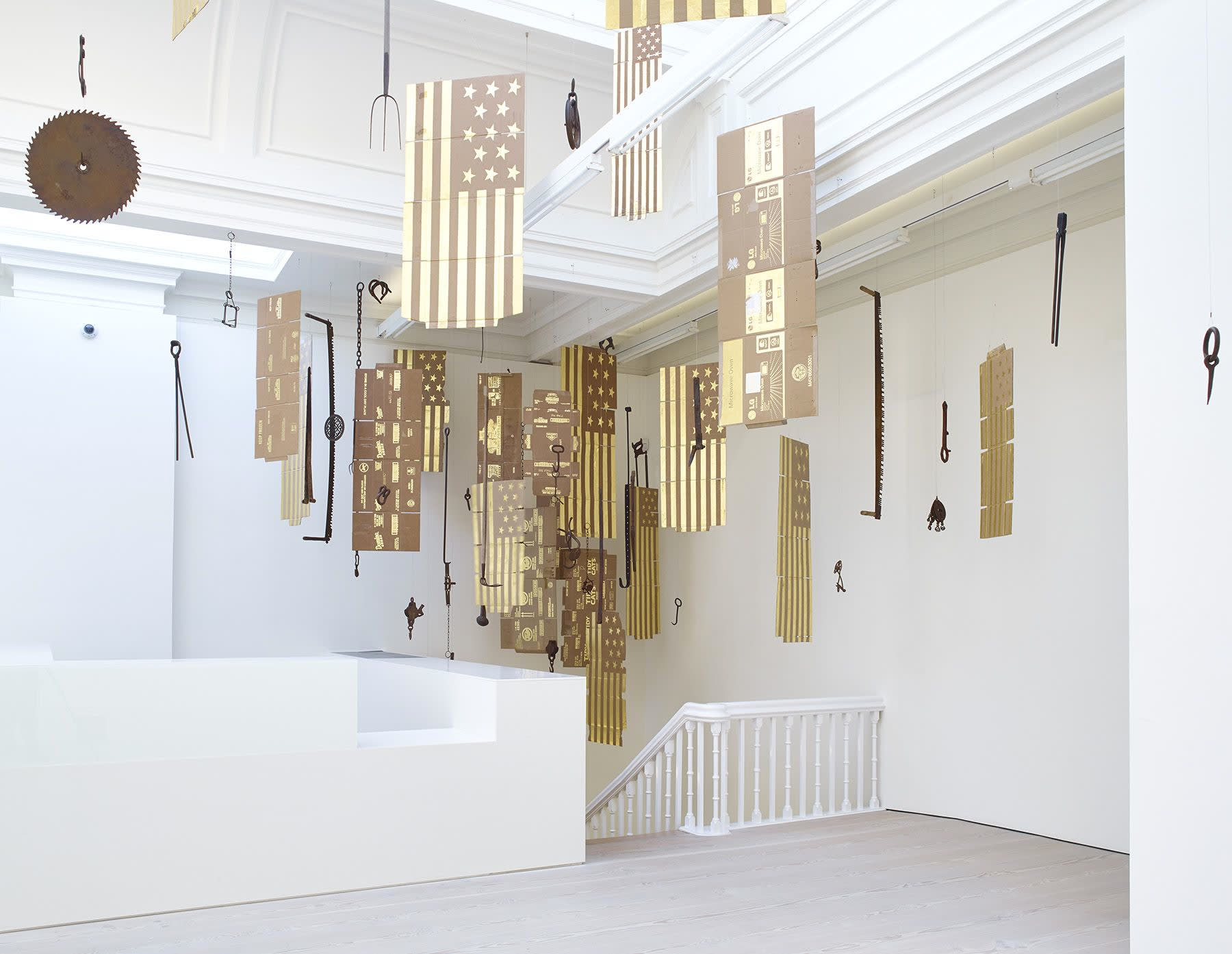 Gallery view of cardboard flags and numerous metal tools suspended from the gallery ceiling.