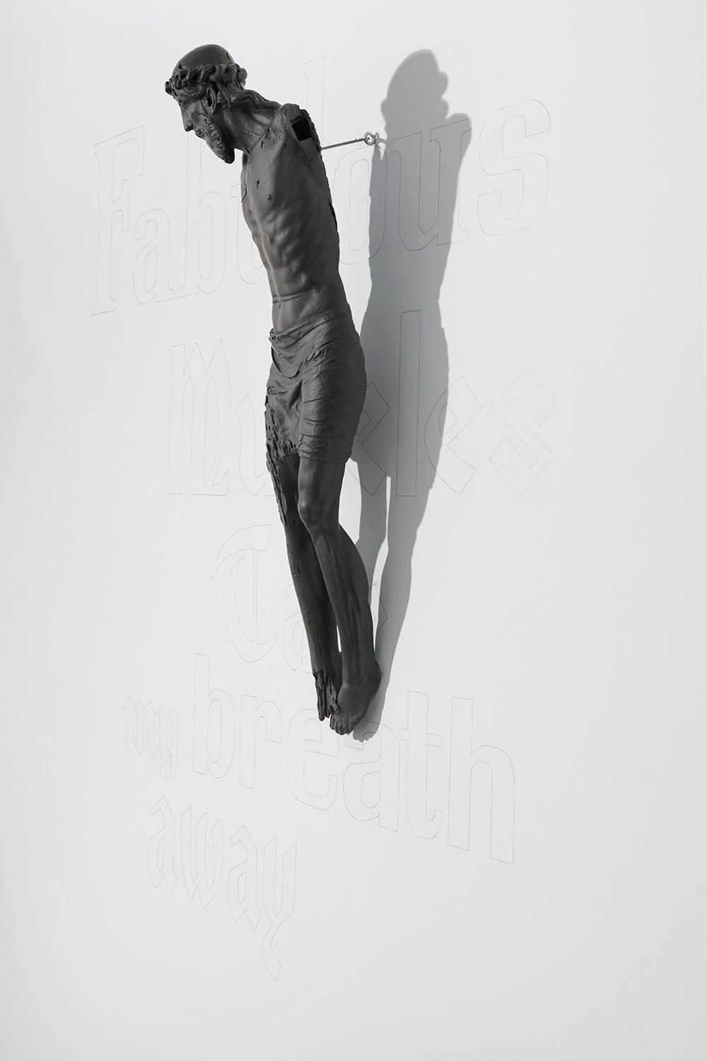 Installation view of a sculpture depicting Jesus crucified, suspended off a gallery wall featuring large faint text.