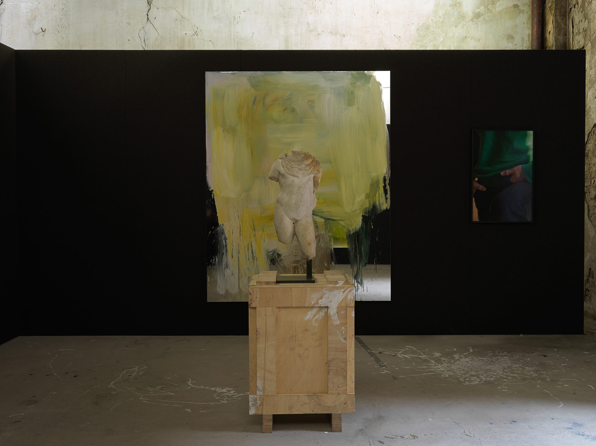 Small headless marble sculpture on top of a crate, placed in front of two colorful artworks.