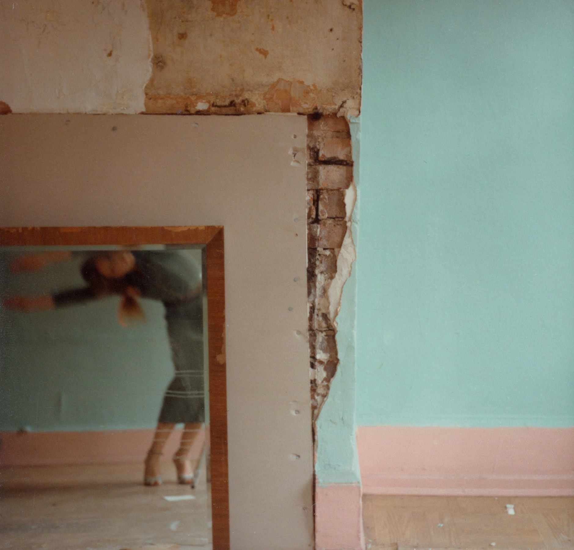 Color photograph of a blue and pink wall with exposed brick and an inlaid mirror, reflecting a blurred bending figure.