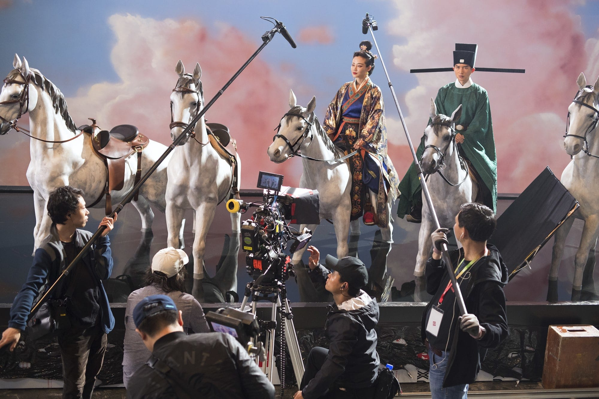 Photograph of five crew members with film equipment documenting a stage set of five horses, two traditionally dressed actors and a backdrop of pink clouds against a blue sky.