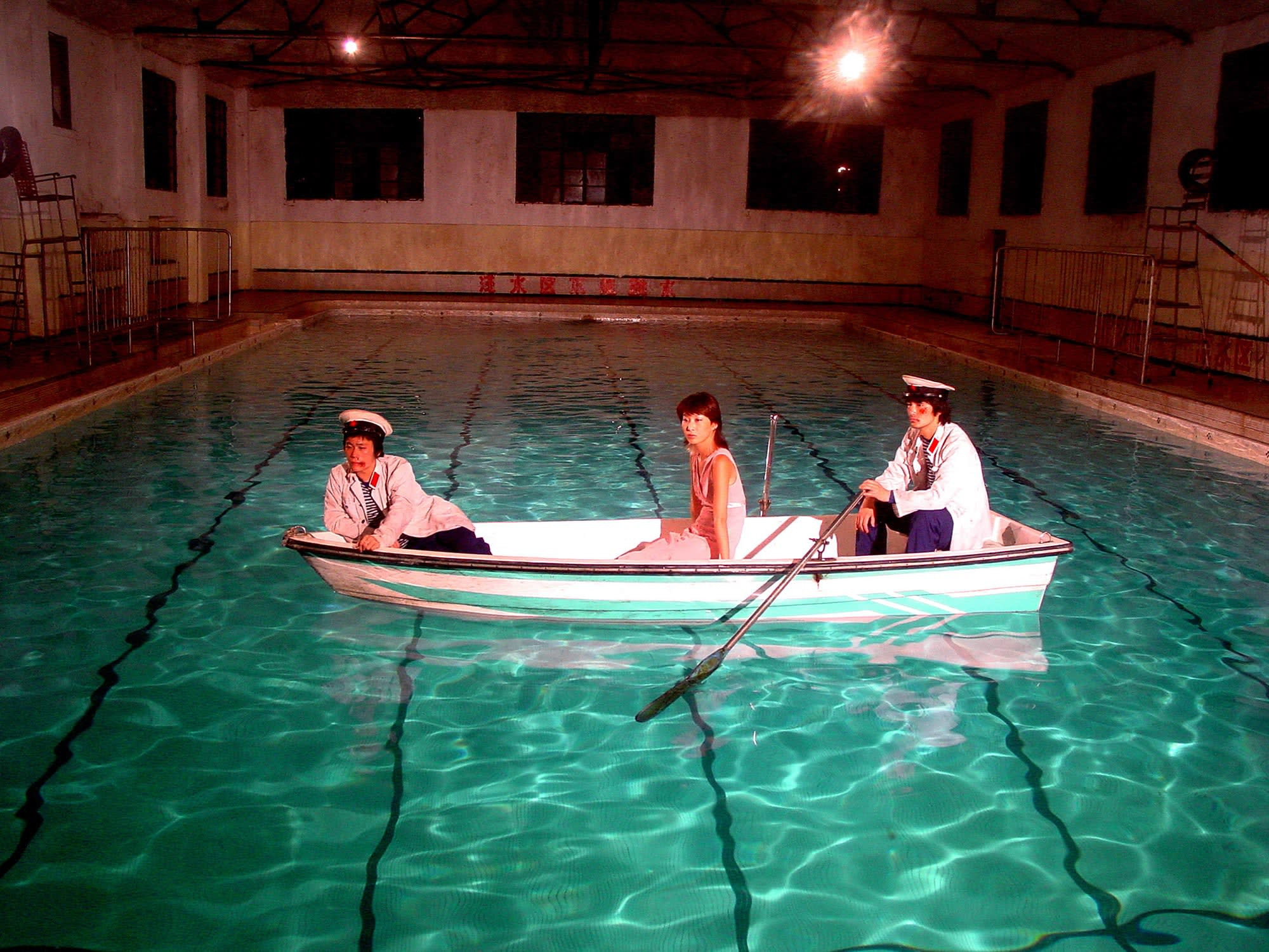Color photograph of three figures seated in a small boat floating in an indoor swimming pool.