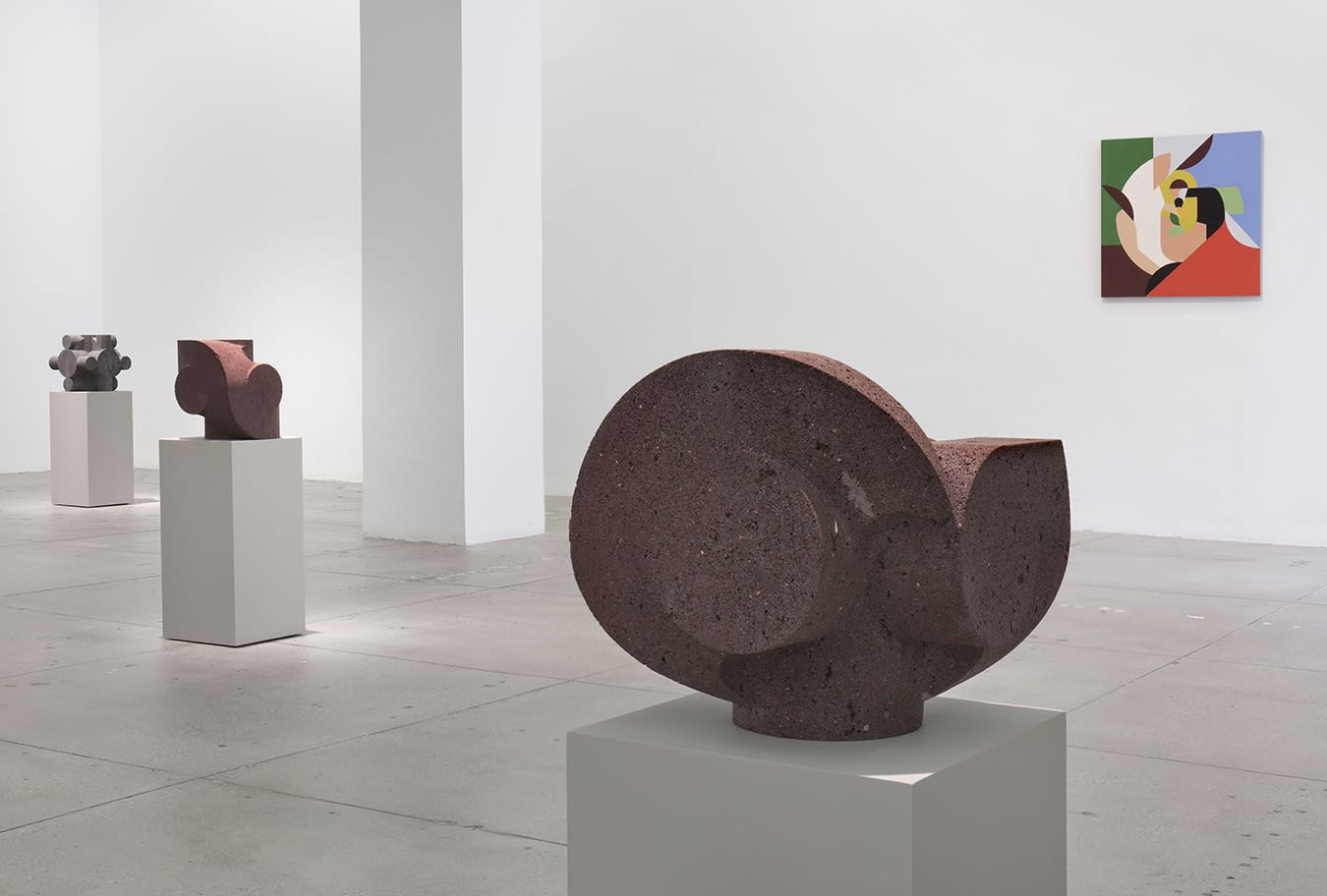 In a large white space, a small abstract painting hangs to the right of 3 small, dark stone sculptures.