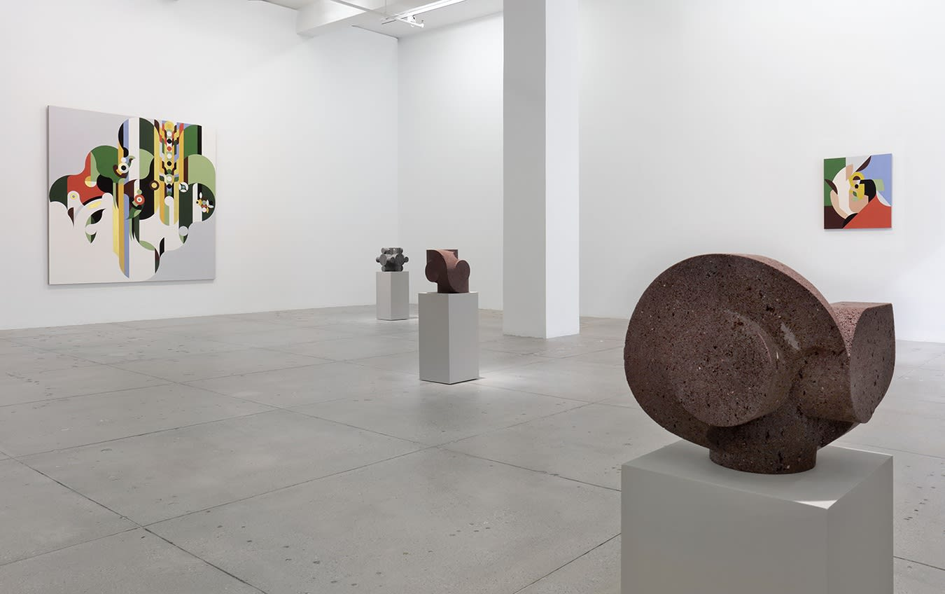 In a large white space, two abstract paintings hang on the wall behind 3 small, dark stone sculptures.