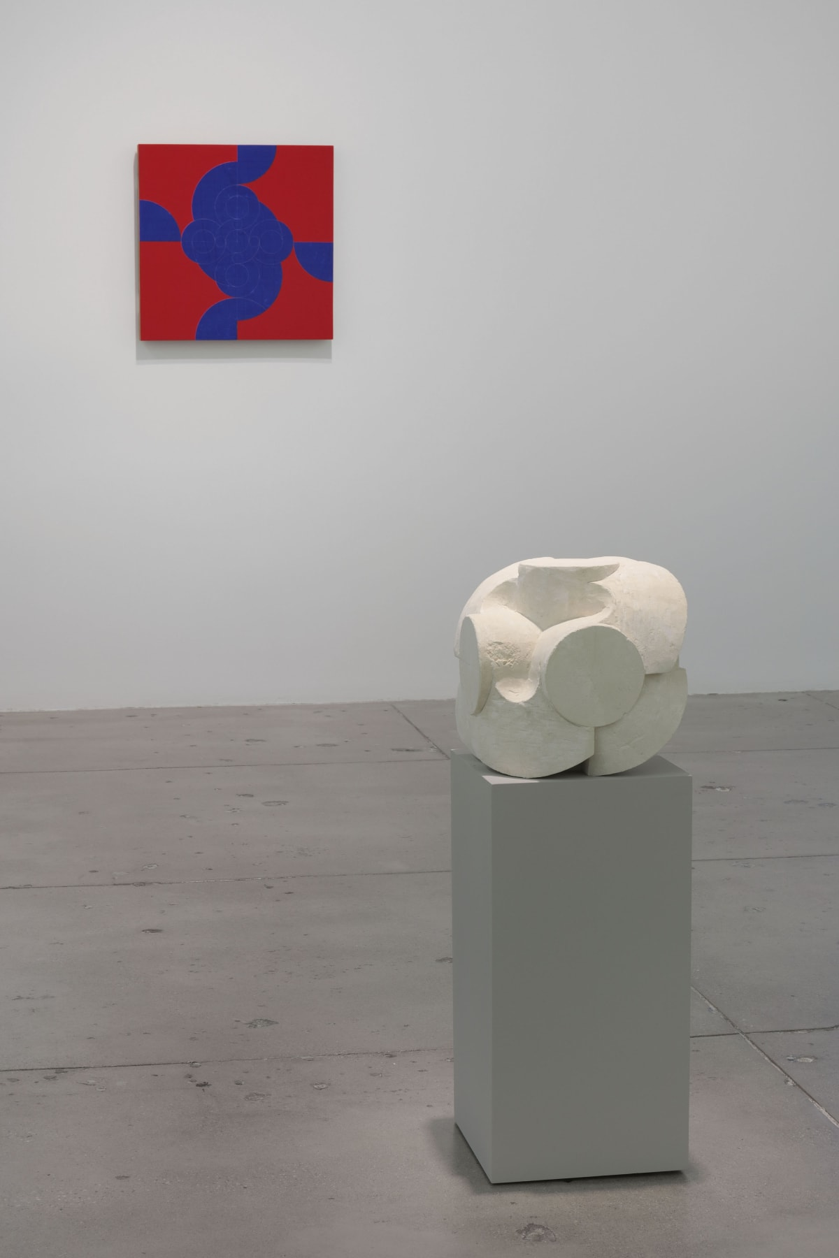 In a large white space, a small red and blue abstract painting hangs on the wall in front of 1 small, white stone sculpture.