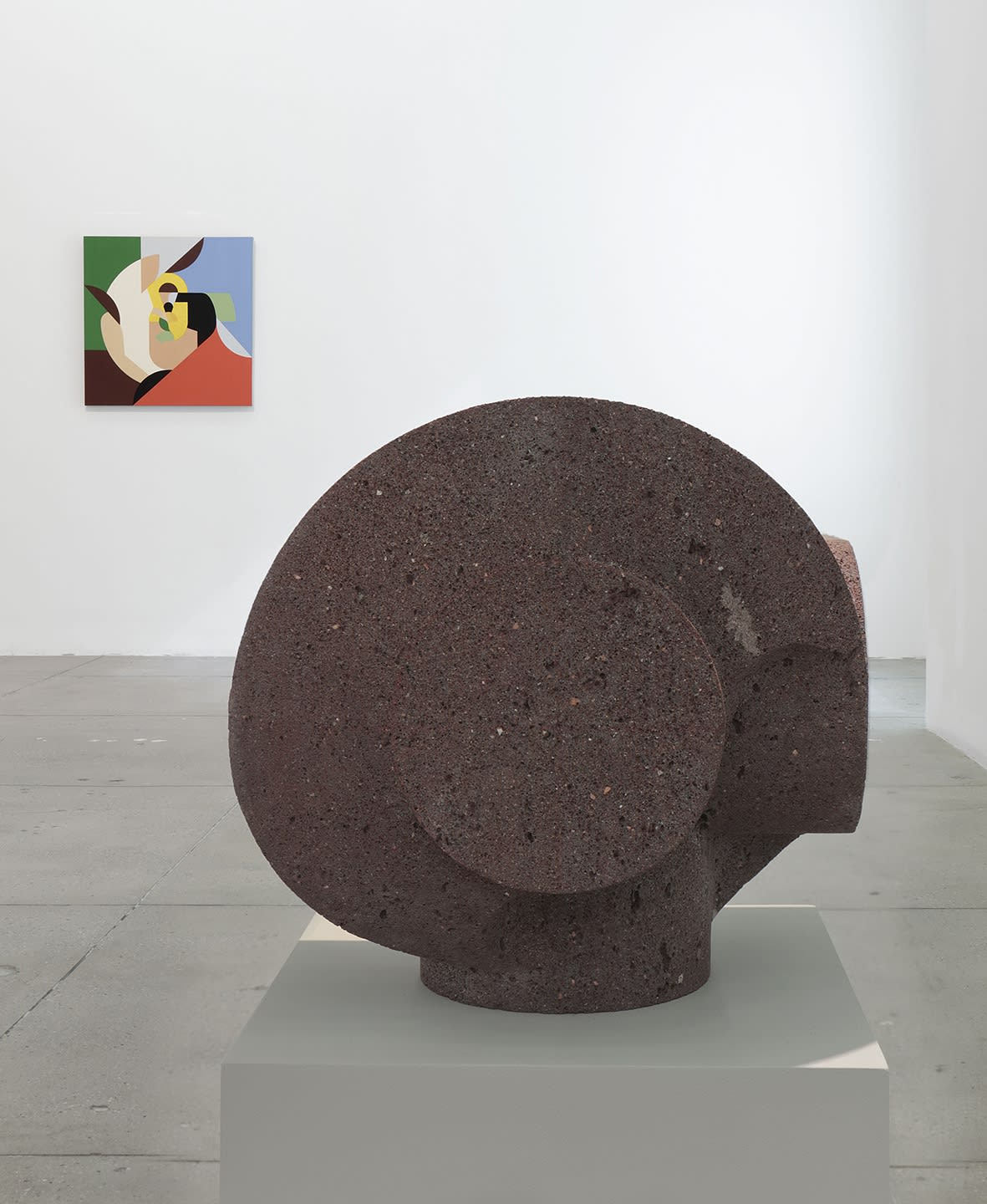1 small stone sculpture stands to the left of a colorful abstract painting on a white wall.
