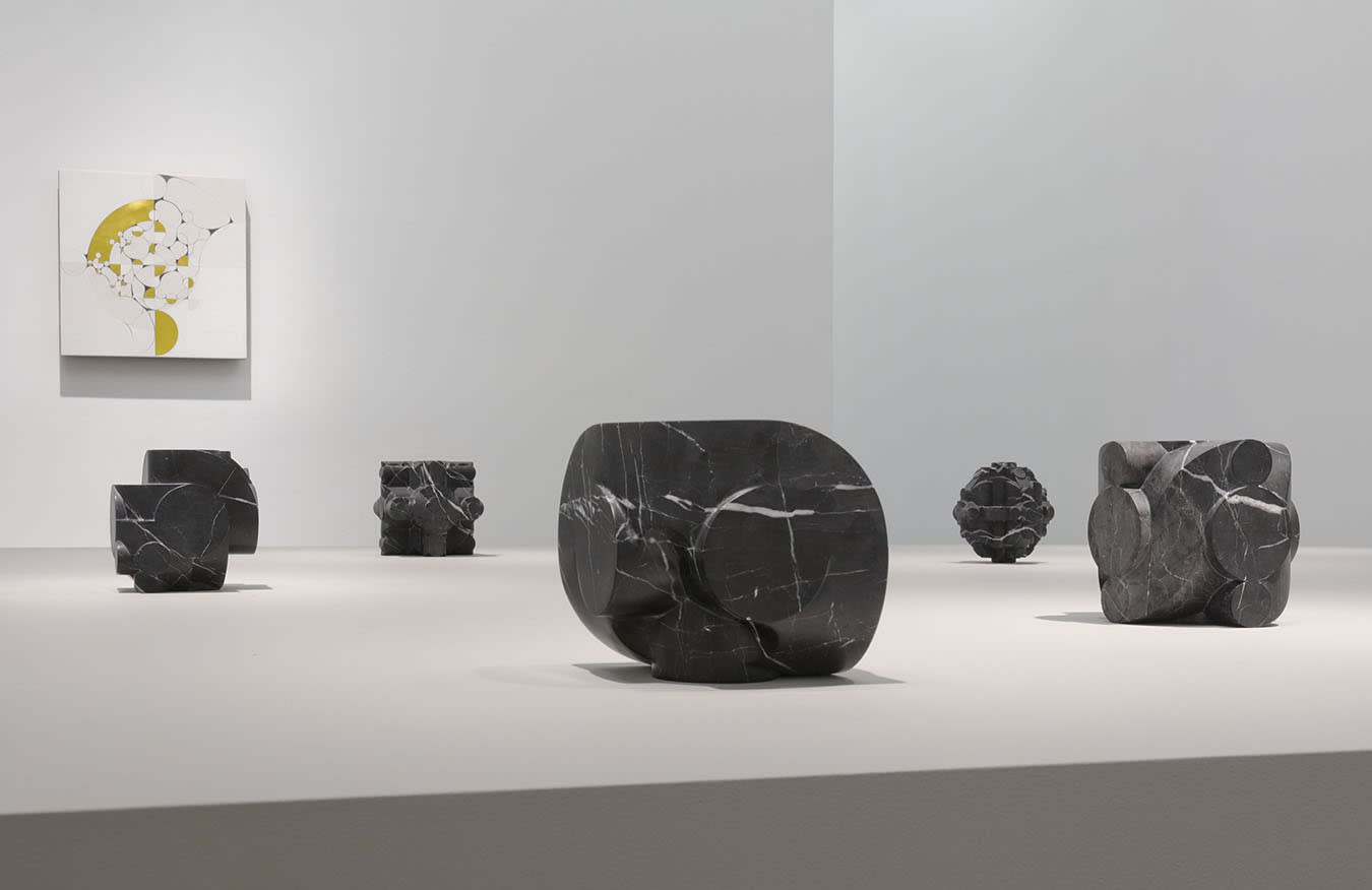 5 small stone sculptures in front of a colorful abstract painting on a white wall.