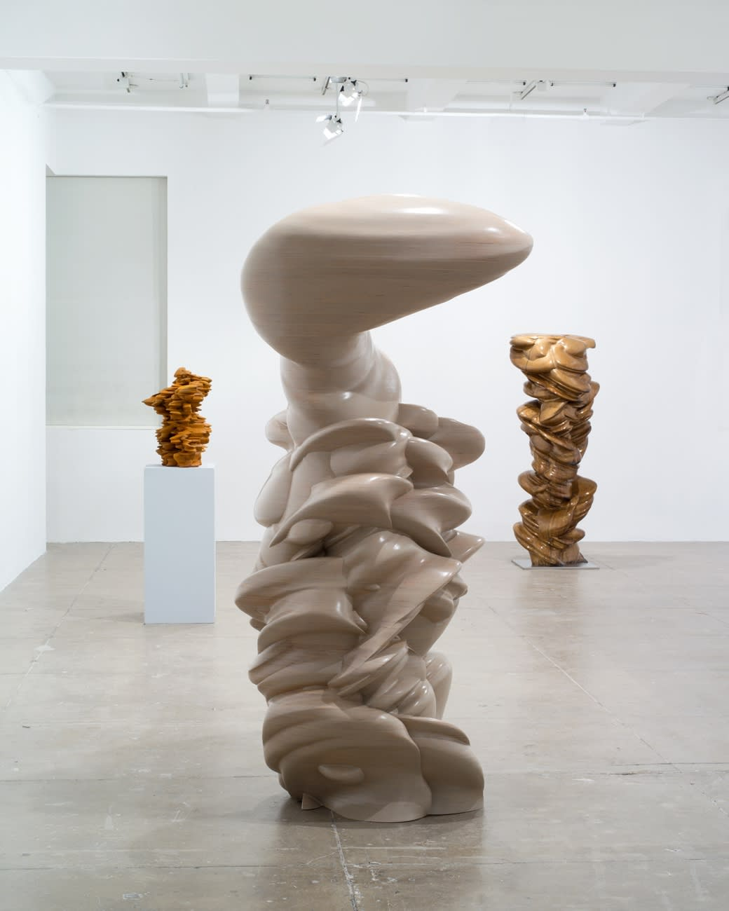Three vertical abstract sculptures stand in a large white room; the sculpture on the left is on a pedestal. They are beige and brown with both smooth and jagged edges.