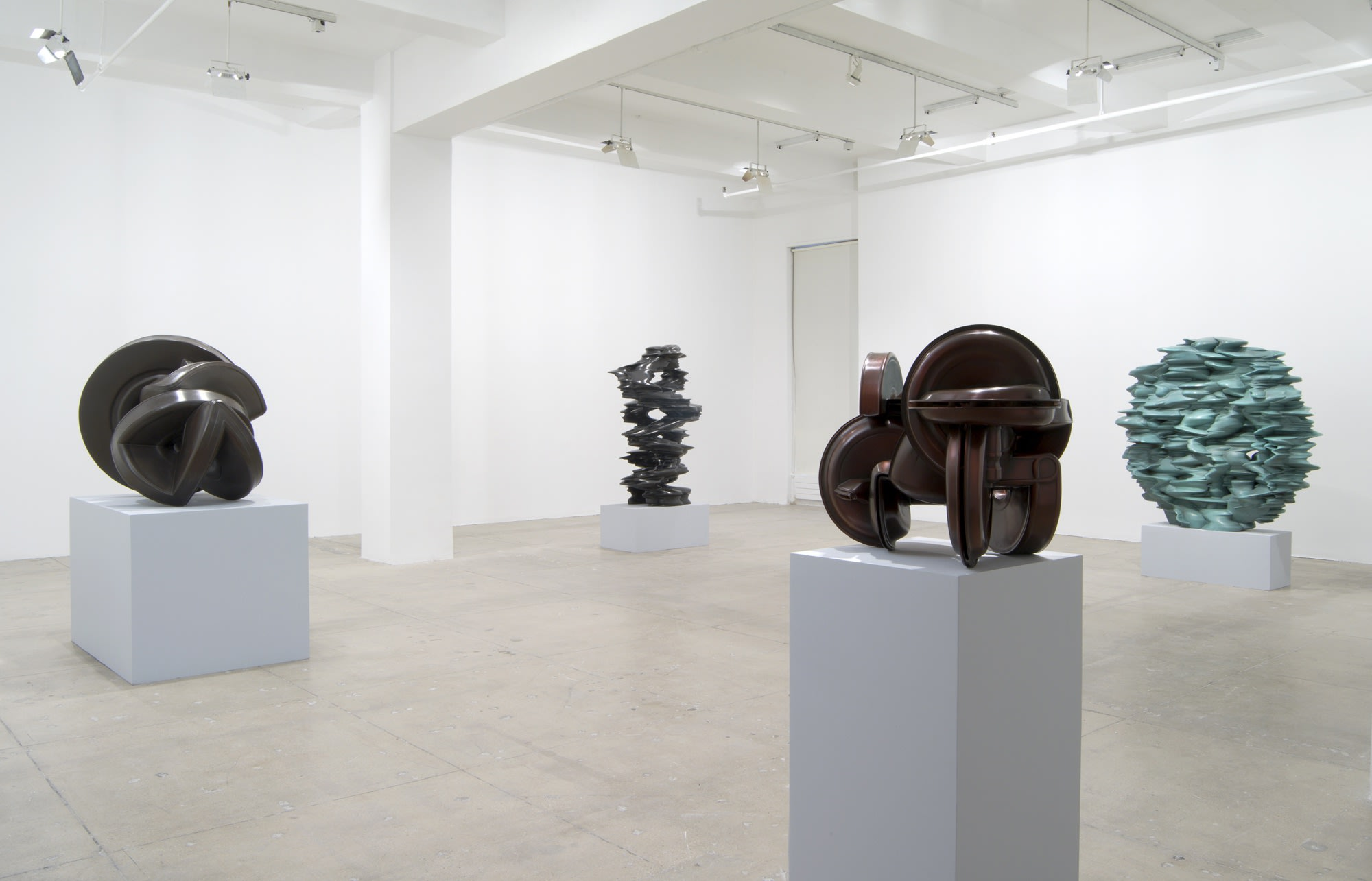 Four abstract sculptures sit on pedestals across a large white room; one on the right is light blue-green and the others are dark brown and grey.