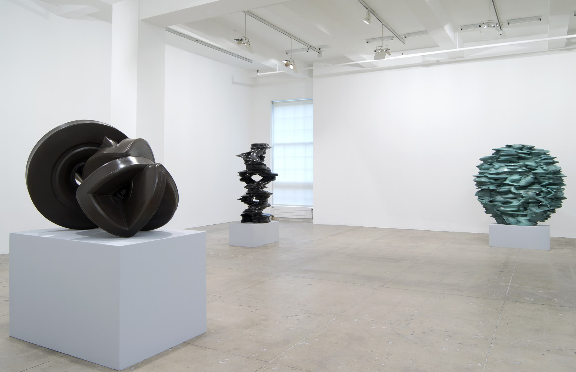 Three abstract sculptures sit on pedestals in a large white room. The one on the right is spherical and light blue-green; the other two are dark grey.