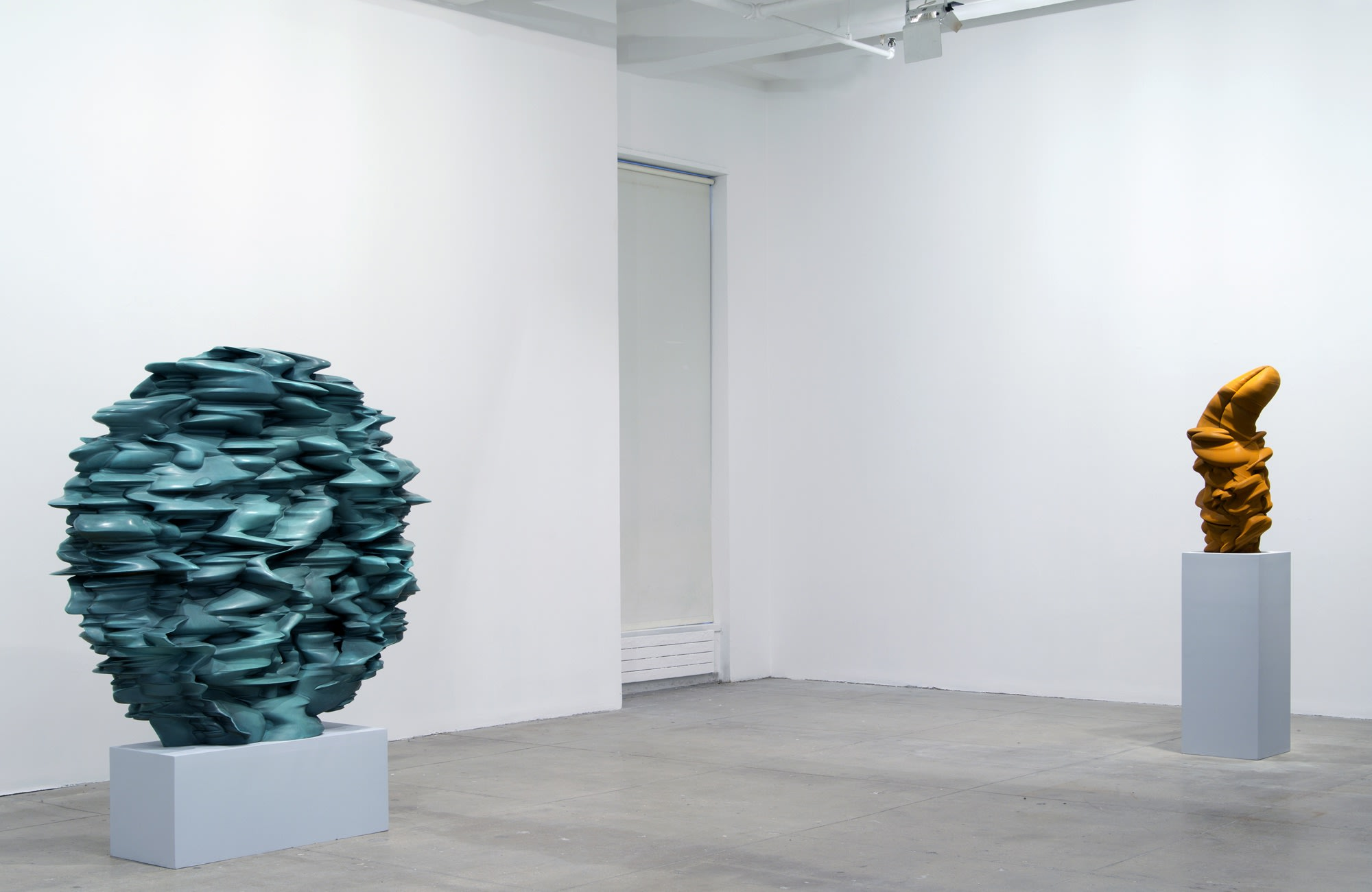 Two abstract sculptures sit on pedestals in a white room. The one on the left is spherical and light blue-green, while on the right the piece is vertical and orange-brown.